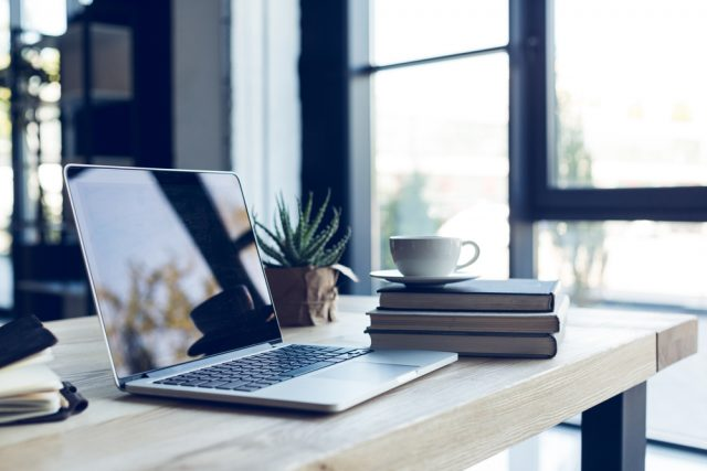 design of workplace with laptop and cup of cofffee in home office
